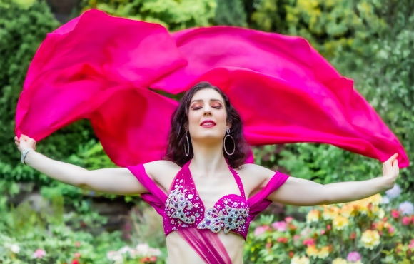 upper body photo of Rachael with arms outstretched, wearing a bright pink costume and holding a pink silk veil behind her