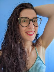 Photo of Rachael smiling at the camera. She is a white woman with long brown hair, wearing large glasses and a blue top.